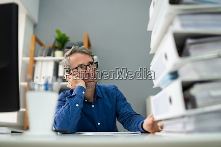 sad men with office paper stack