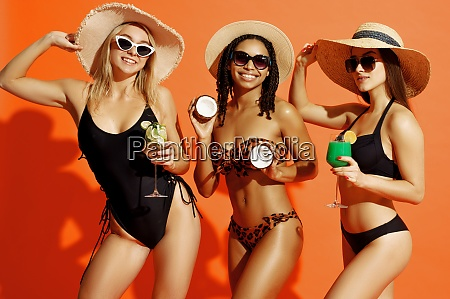 happy girlfriends in swimsuits poses with