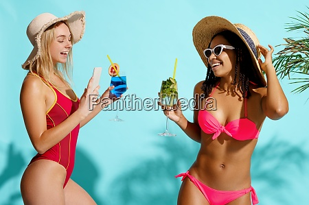 smiling women in swimsuits poses with