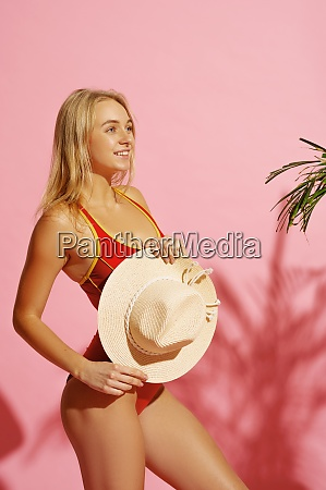 young woman in swimsuit holds hat