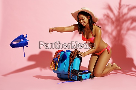 happy woman in swimsuit unpacks suitcase