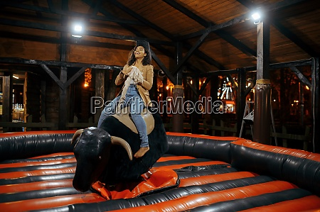 woman on rodeo attraction in night