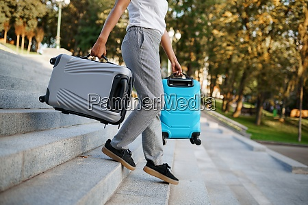 woman carries two suitcases by the