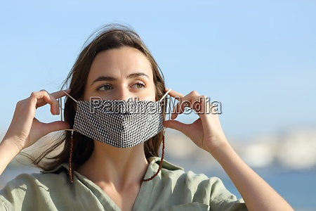 happy woman taking off mask due