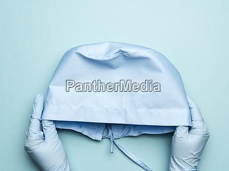 hand hold blue textile medical cap