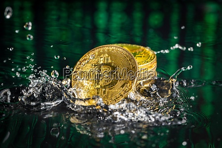 gold bitcoin coin falling to water