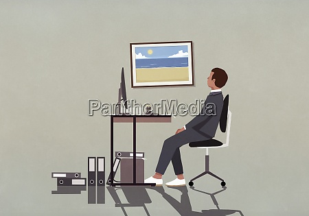 businessman at office desk looking at
