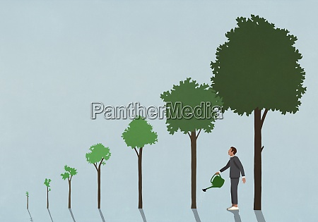businessman watering growing trees with watering