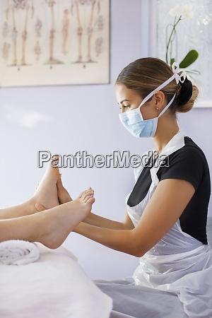 female masseuse in face mask massaging