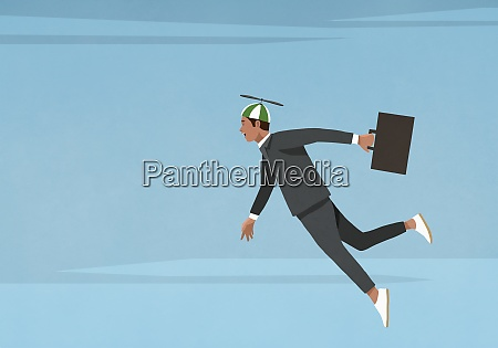 businessman in propellor hat flying in
