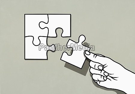 hand finishing jigsaw puzzle with missing