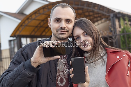 portrait young couple with camera phones