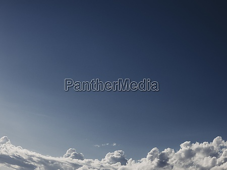 cloud formations against sunny blue sky