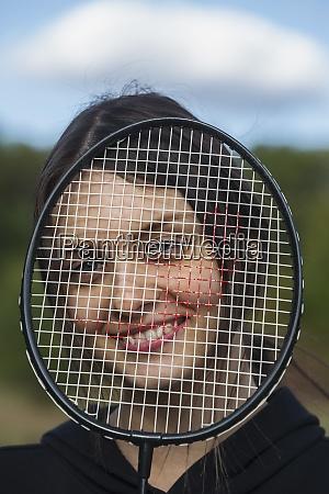 portrait happy young woman behind badminton