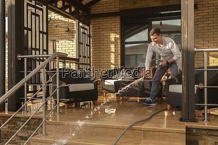man spraying patio with hose