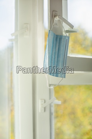 face mask hanging from window latch
