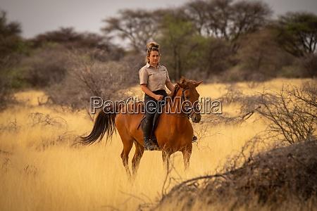 blonde rides horse in grassland near