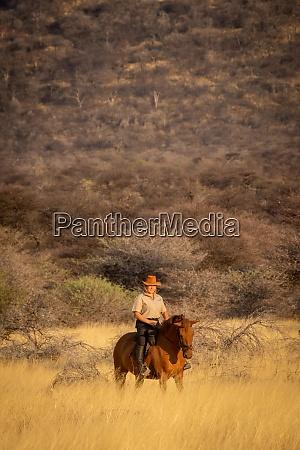 blonde rides horse through grass near