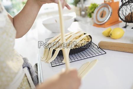 woman arranging lattice crust over apple