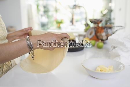 woman rolling pie crust dough in