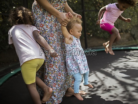 mother and daughters playing on trampoline