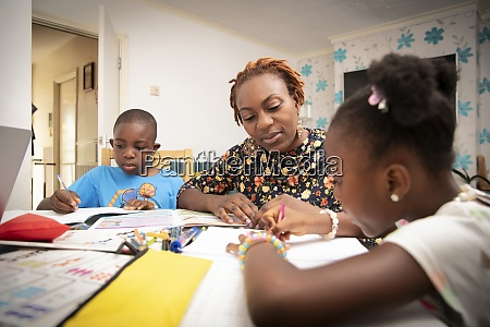mother helping kids with homework at