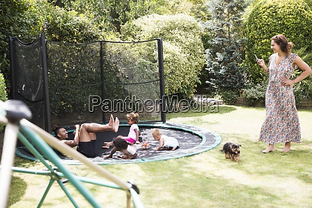 family playing on sunny backyard trampoline