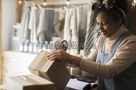 female shop owner preparing box for