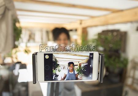 female shop owner filming vlog with
