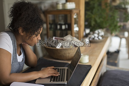 female shop owner using laptop at