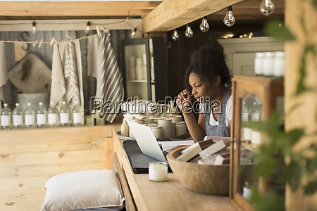 female shop owner working at laptop