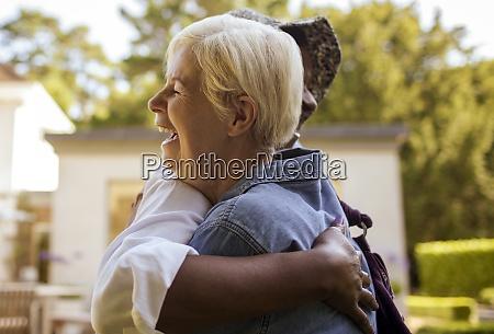 happy senior women friends hugging on