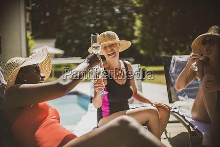 happy senior women friends toasting champagne