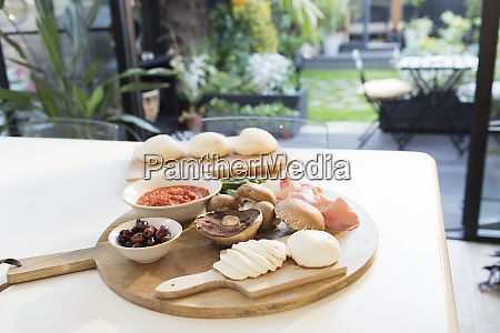 fresh pizza ingredients on cutting board