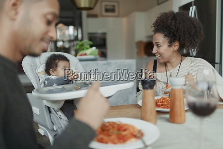 happy parents and baby daughter eating