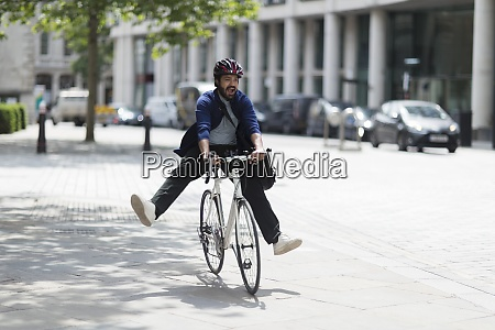 playful man riding bicycle on sunny