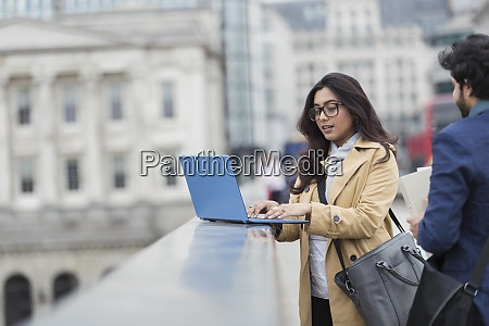 business people using laptop on city