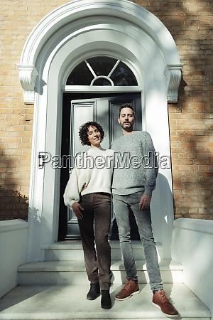 portrait confident couple at arched front