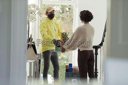 woman receiving grocery delivery from courier