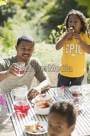 father and children enjoying garden lunch