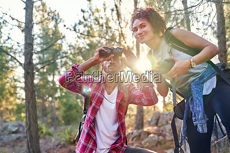 curious young hiker couple using binoculars