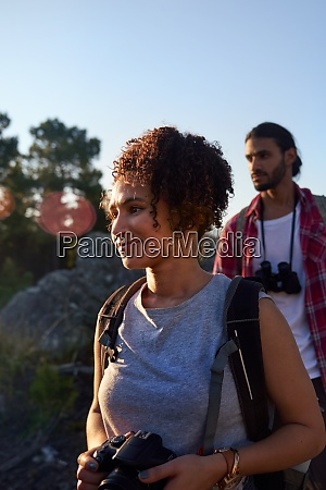 young couple hiking with camera
