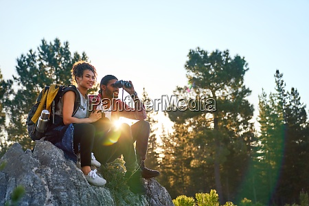 young couple hiking with binoculars on