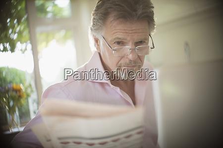 senior man reading newspaper at laptop