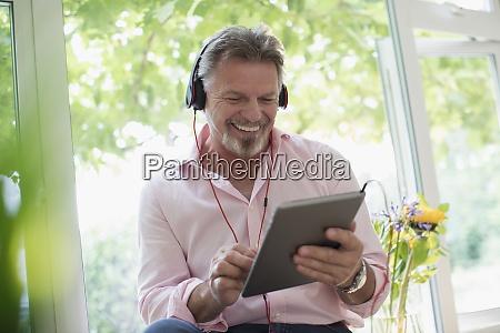 happy senior man using headphones and