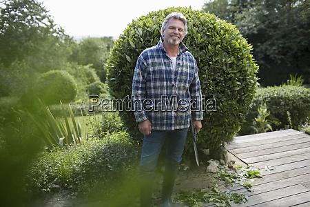 portrait happy senior man gardening on
