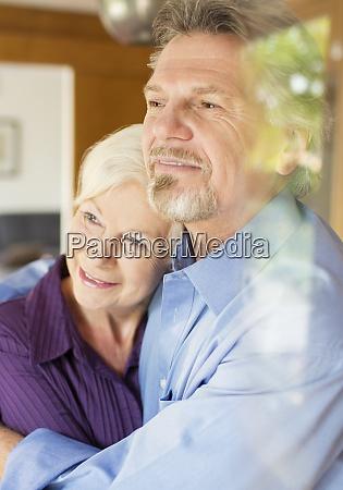 serene senior couple hugging at window