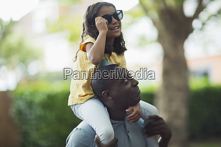 father carrying daughter with sunglasses on