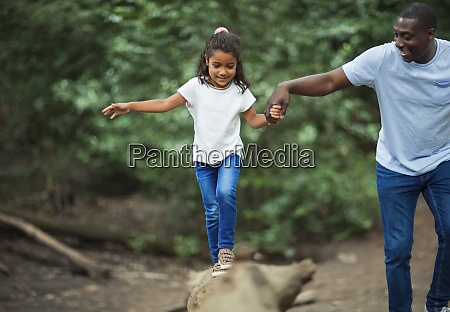 father helping daughter balance on fallen