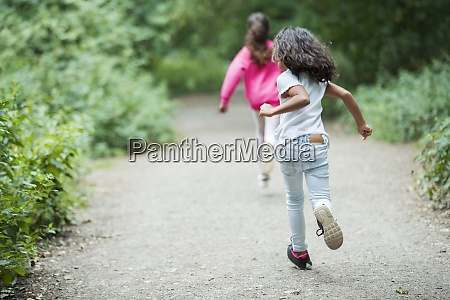 carefree sisters running on park path